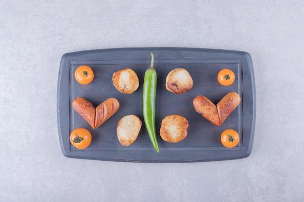 Saucisses frites et pommes de terre à bord sombre.