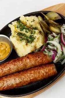 Saucisses frites avec purée de pommes de terre. un plat traditionnel appétissant dans une poêle en fonte. fermer. verticale.
