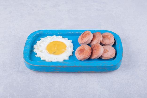 Saucisses frites tranchées et oeuf sur plaque bleue.