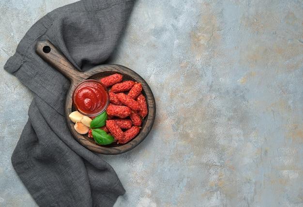 Saucisses fumées à l'ail et ketchup sur une plaque en bois avec une poignée sur un bureau gris avec une serviette. bureau culinaire avec espace pour copier.