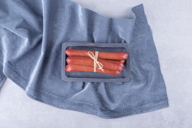 Saucisses fumées attachées avec une corde sur une planche sombre.