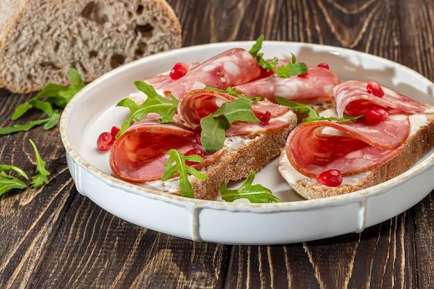 Saucisses fumées et sandwichs au fromage à la crème sur une assiette. décoré avec des herbes à l'aneth. sur un fond en bois sombre. copiez l'espace.