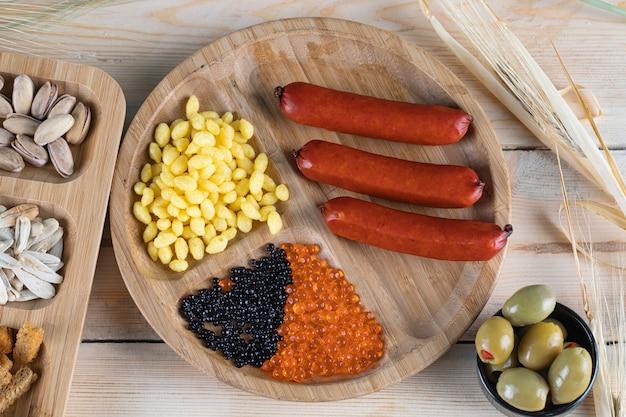 Saucisses, graines de maïs marinées et olives
