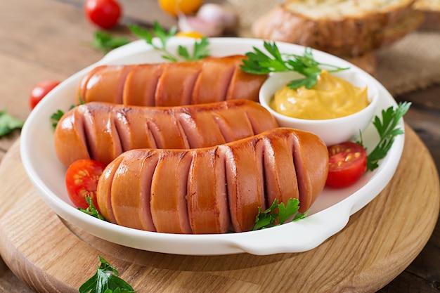 Saucisses sur le gril sur la table en bois