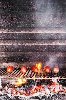 Saucisses sur le grill avec des flammes