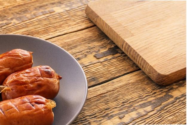 Saucisses grillées sur assiette et planche à découper en bois sur de vieilles planches. vue de dessus.