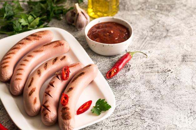 Saucisses grillées au ketchup, aux herbes et aux piments