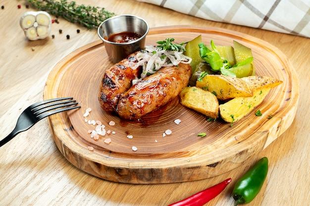 Saucisses grillées au miel et sauce à la bière servies sur une planche de bois avec des herbes, des pommes de terre frites, des concombres marinés et du chou. cuisine maison allemande et bavaroise. mise au point sélective