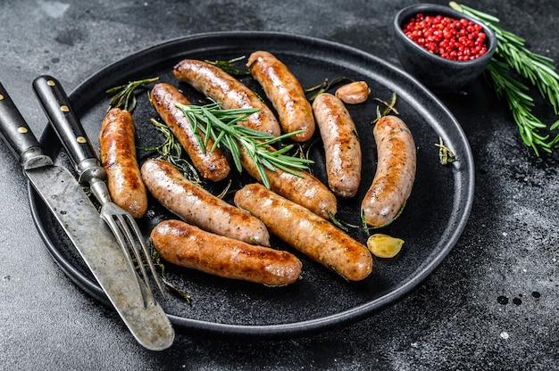Saucisses grillées aux herbes de romarin, viande de bœuf et de porc. fond noir. vue de dessus.