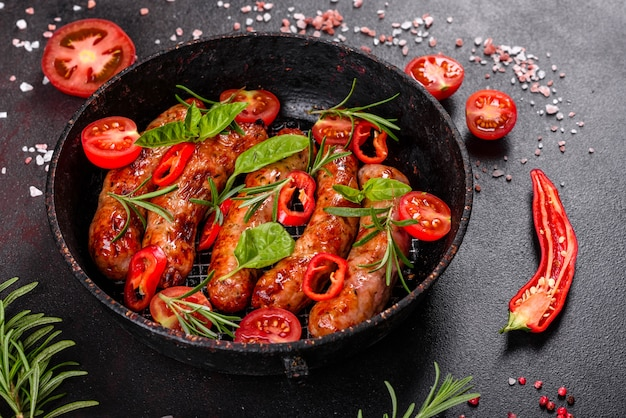 Saucisses grillées aux légumes et épices sur fond noir