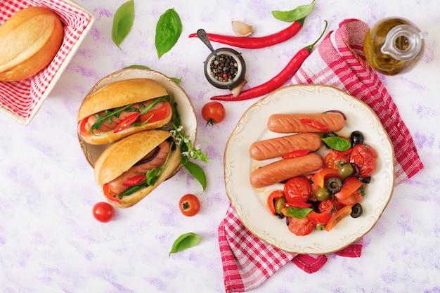 Saucisses grillées aux légumes à la grecque sur plaque.
