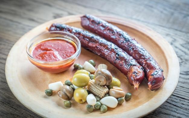 Saucisses grillées aux légumes marinés