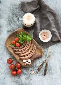 Saucisses grillées aux légumes sur une planche de service rustique et une tasse de bière légère sur fond grunge.