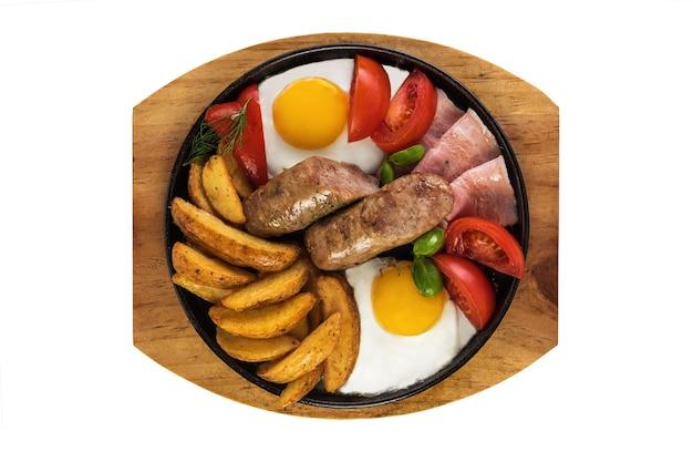 Saucisses grillées avec bacon et œufs brouillés et pommes de terre rustiques épicées. isolé