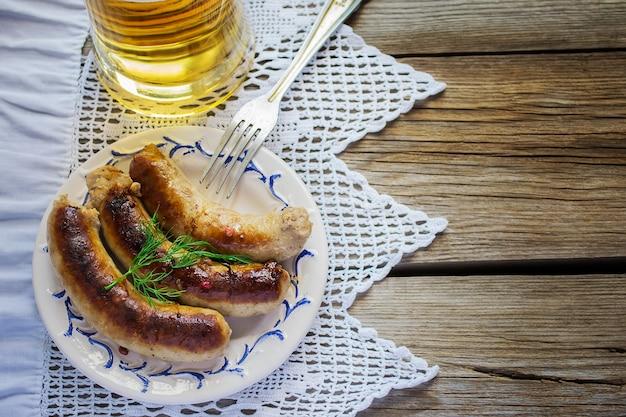 Saucisses grillées à la bière sur un fond en bois. mise au point sélective