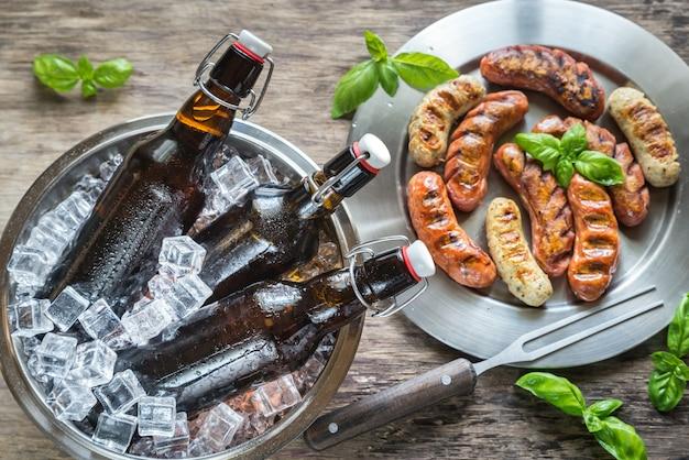 Saucisses grillées avec des bouteilles de bière