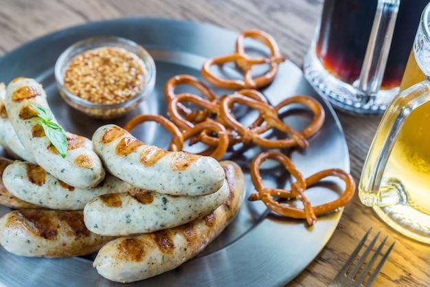 Saucisses grillées avec bretzels et chopes de bière