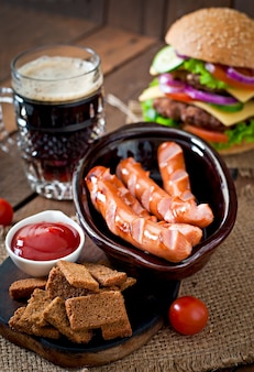 Saucisses grillées, craquelins et bière sur une table en bois de style rustique.