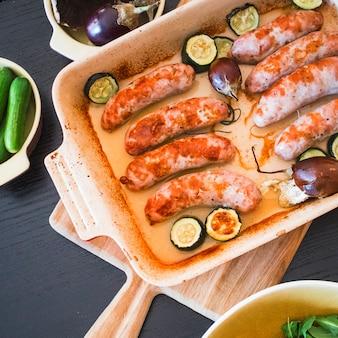 Saucisses grillées dans un plat allant au four avec des légumes