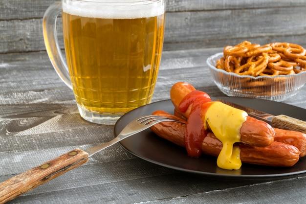 Saucisses grillées avec du ketchup et de la moutarde sur une table en bois.