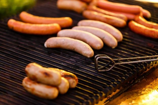 Saucisses grillées sur le gril avec fumée et flammes en soirée, mise au point sélective