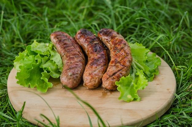 Saucisses grillées et légumes sur un vieux plateau en bois