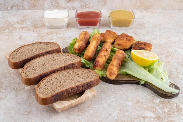 Saucisses grillées avec nuggets de poulet sur un morceau de laitue sur une planche en bois avec sauces de côté.