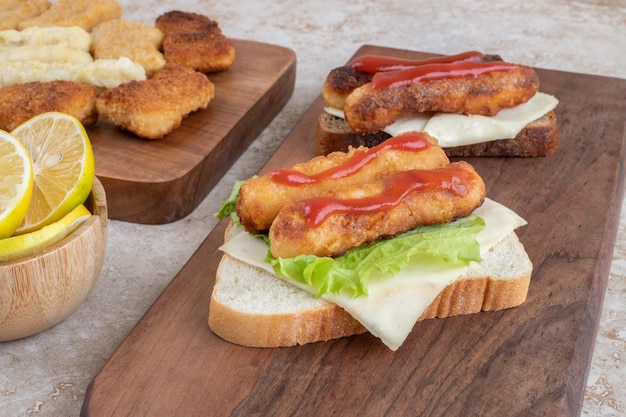 Saucisses grillées et nuggets de poulet sur des toasts de sandwich aux herbes et épices sur un plateau en bois.