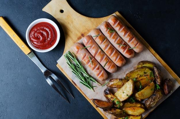 Saucisses grillées sur une planche à découper en bois.