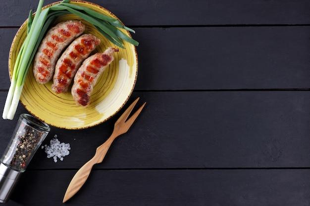 Saucisses grillées sur plaque jaune.