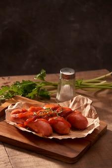 Saucisses grillées avec sauce ketchup sur une table en bois