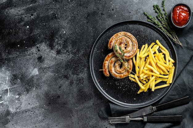 Saucisses grillées en spirale de porc allemand traditionnel avec un plat d'accompagnement de frites. fond noir