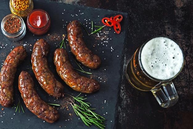Saucisses grillées sur un tableau de pierre sombre avec un verre de bière