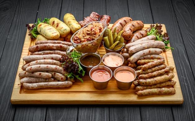 Saucisses grillées avec verre de bière sur une table en bois