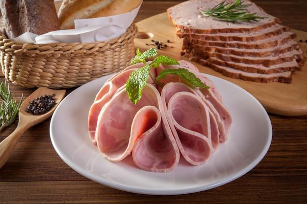 Saucisses jambon et légumes sur la table en bois