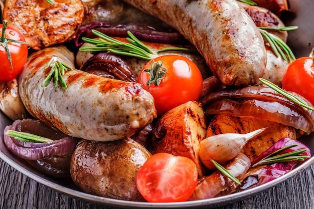 Saucisses et légumes grillés dans un style rustique.