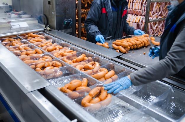 Saucisses. ligne d'emballage de saucisses. fabrication industrielle de produits à base de saucisses.