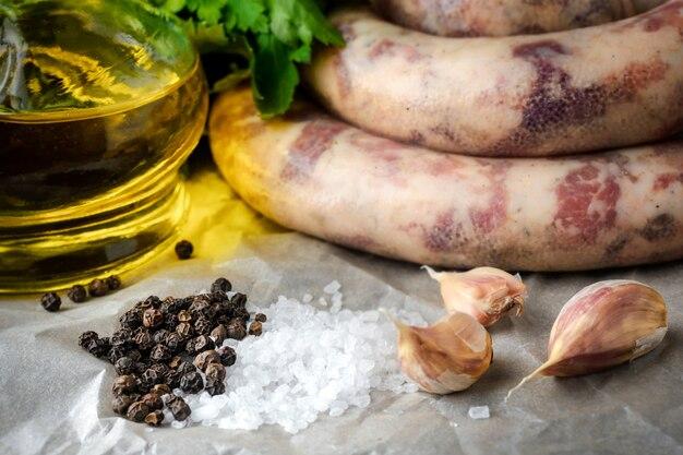 Saucisses maison, ail, persil et huile d'olive sur la table.