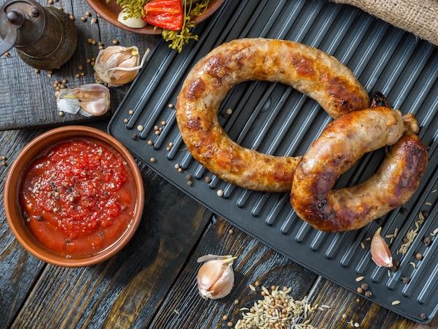 Saucisses maison épicées saucisses de porc et de boeuf grillées avec sauce, épices et concombre mariné