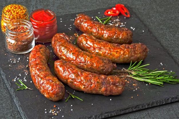Saucisses de munich juteuses grillées avec des épices sur un plateau en pierre noire