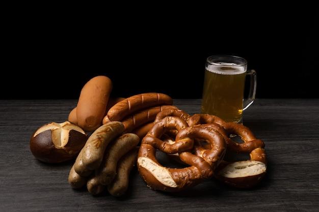Saucisses oktoberfest bretzels et bière avec fond sombre et table en bois