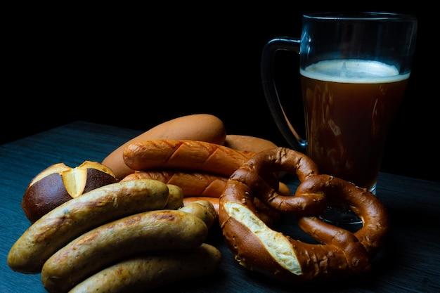Saucisses oktoberfest et pain bretzel avec pot de bière sur table en bois nourriture sombre