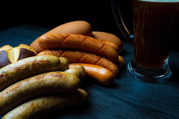 Saucisses et pain bretzel oktoberfest avec pot de bière sur table en bois de style alimentaire sombre
