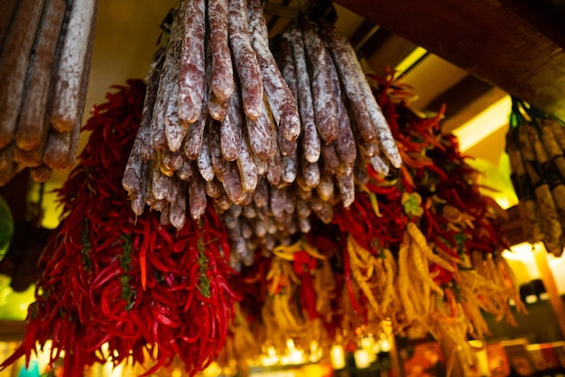 Saucisses et poivrons suspendus dehors au marché rural traditionnel