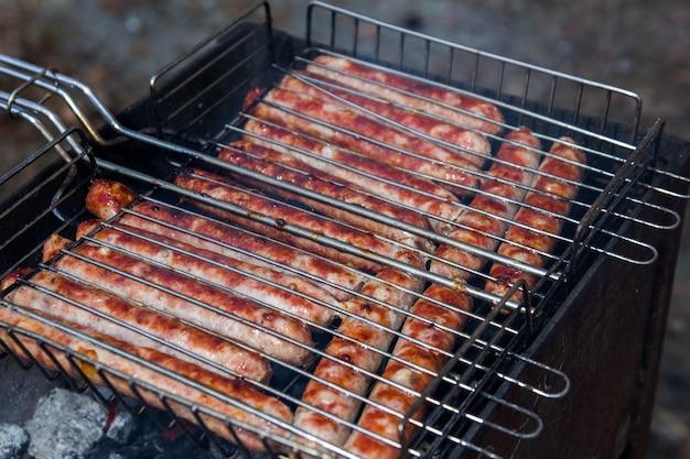 Saucisses de porc barbecue en plein air sur le gril
