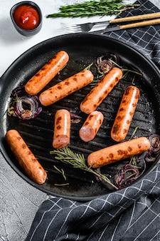 Saucisses de porc classiques grillées avec oignon, ail et romarin dans une poêle