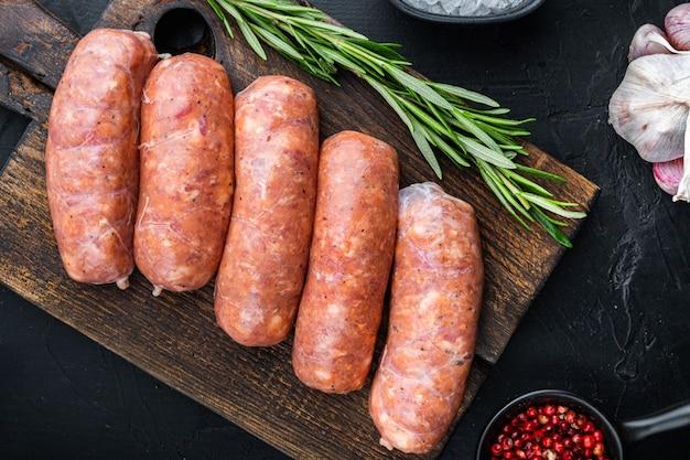 Saucisses de porc crues traditionnelles, à plat, sur fond noir