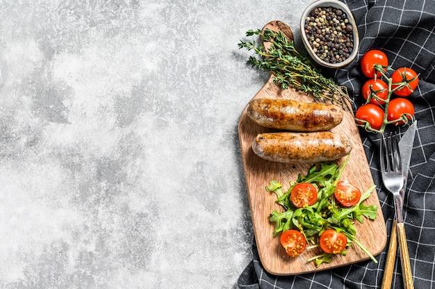 Saucisses de porc grillées au barbecue avec un accompagnement de salade de tomates