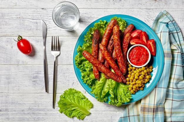 Saucisses de porc italiennes courtes chipolata grillées et servies sur une assiette bleue avec du ketchup et des tomates cerises, de la laitue verte et des pois sur une surface en bois blanche, vue de dessus, gros plan
