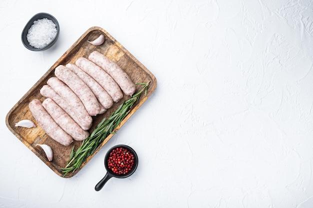 Saucisses de poulet crues, à plat avec un espace réservé au texte, sur fond blanc